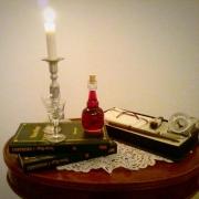 Liquore all'uva americana, ambientazione retrò con libri, calamaio e candelabro