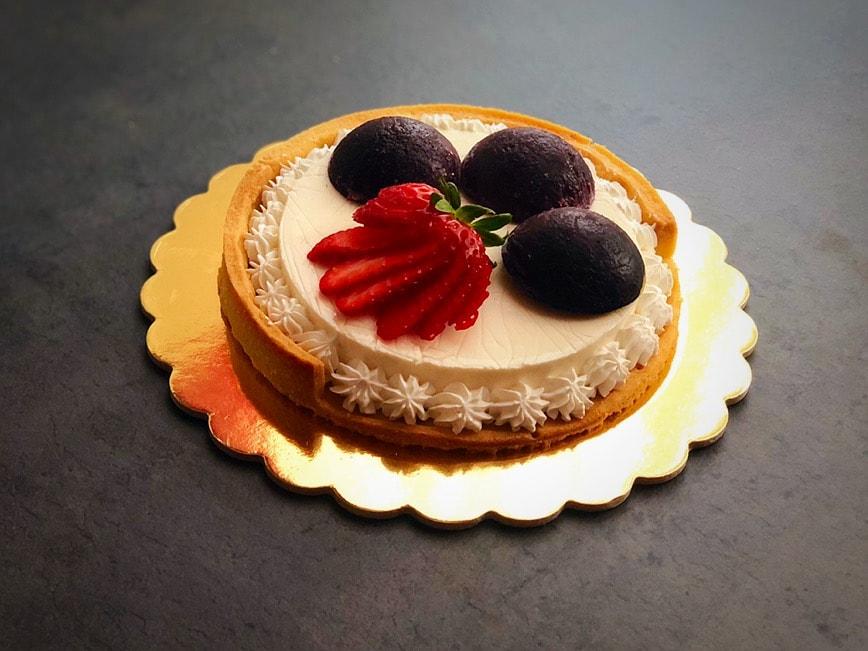 crosfruit crostata con panna cotta e geléai mirtilli e frutti rossi, decorata con fragola e ciuffi di panna fresca