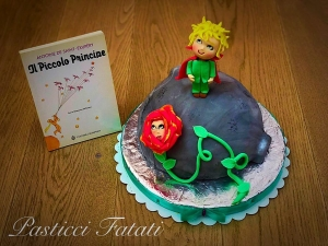 torta del pianeta del piccolo principe con una copia del libro