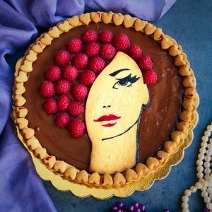 primo piano del dolce eleganza al cioccolato e lamponi, vista dall'alto del profilo femminile con i lamponi