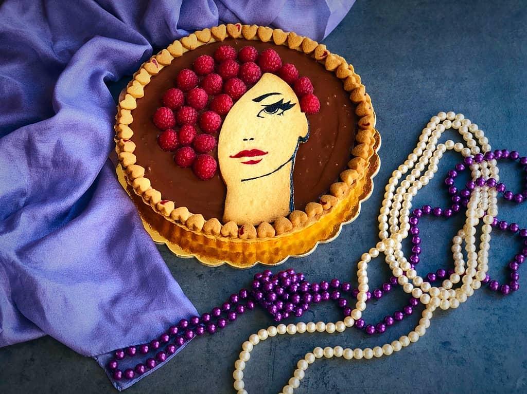 Crostata eleganza al cioccolato e lamponi con profilo femminile