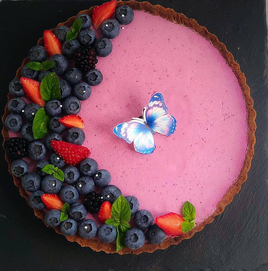 Crostata alla fragola con panna cotta alle more e mirtilli decorata con frutta fresca e farfalla di ostia