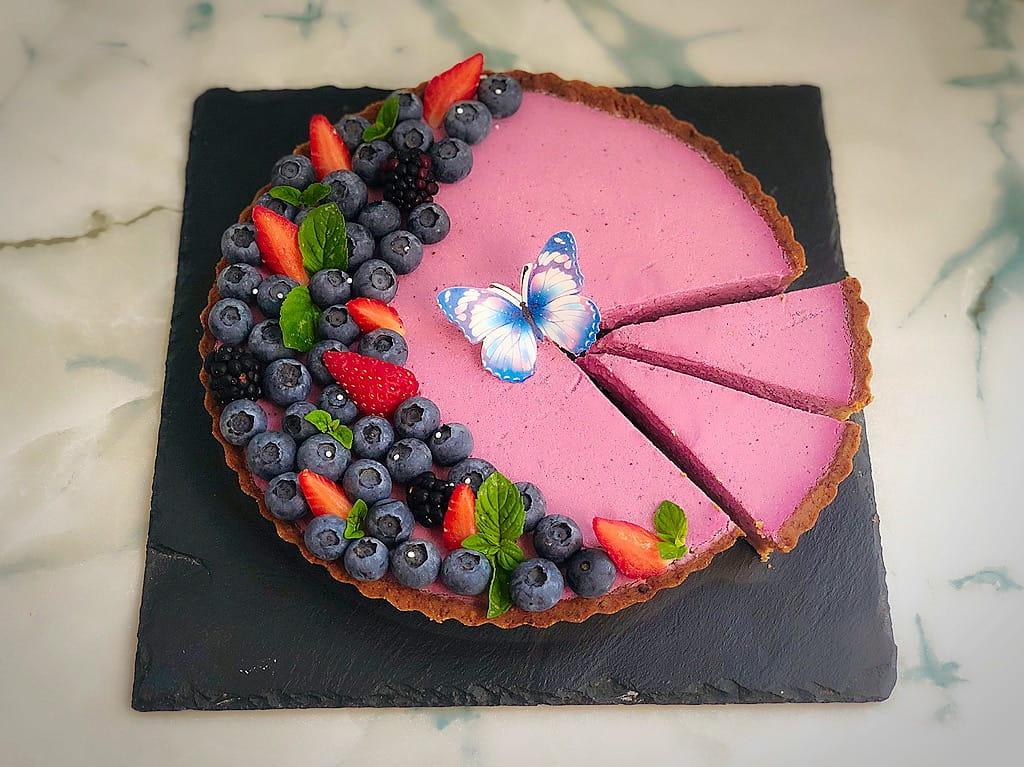 crostata con panna cotta alle more e mirtilli decorata con frutta e fette tagliate