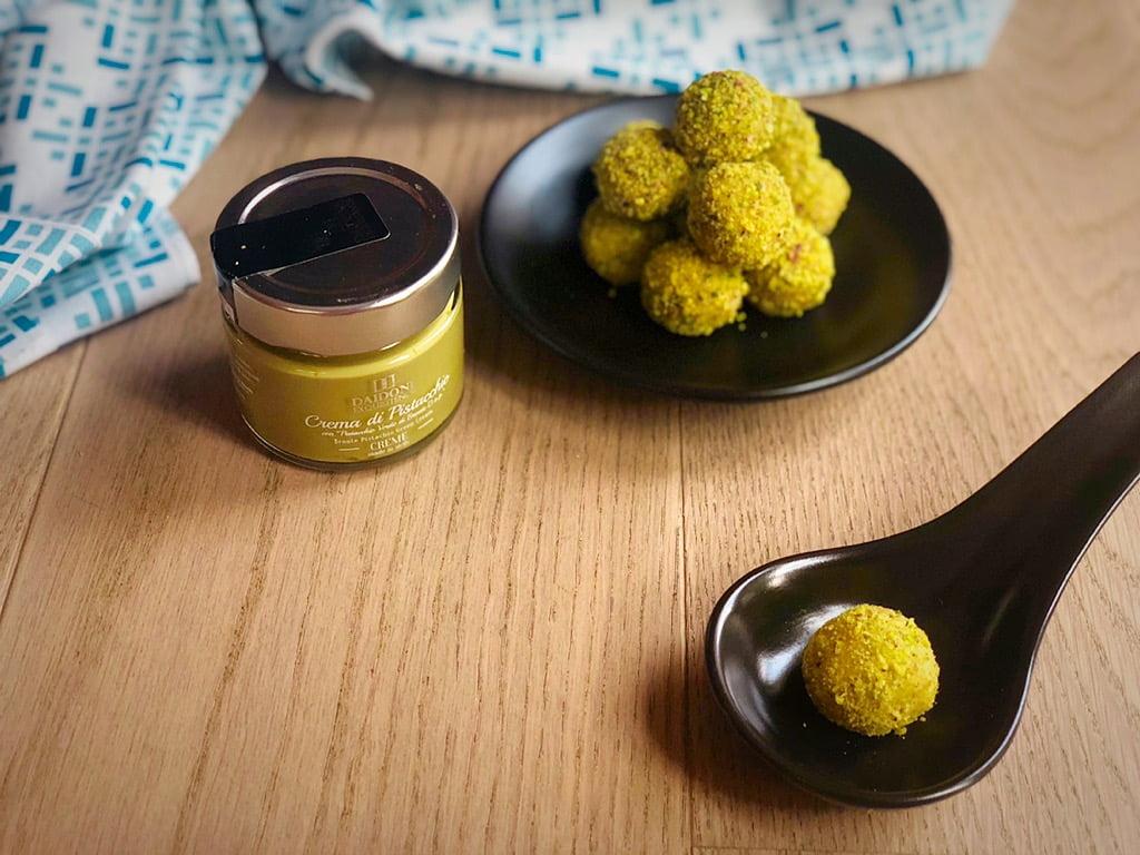 tartufi al pistacchio, singolo su cucchiaio ed in secondo piano piattino e crema daidone
