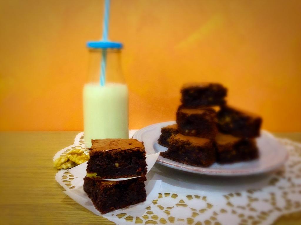 brownies alle noci, due pezzi in primo piano e gli altri sullo sfondo con bottiglia di latte